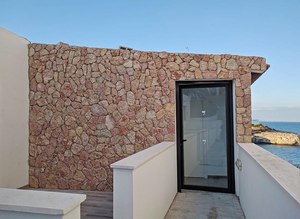 Revestimiento decorativo de piedra en pared exterior de hotel en Cala Murada Mallorca